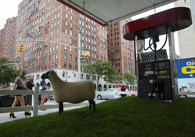 People walk by 'Sheep Station' in the Chelsea neighbourhood of New York. The piece is an art installation at a former petrol pump by Francois-Xavier Lalanne.