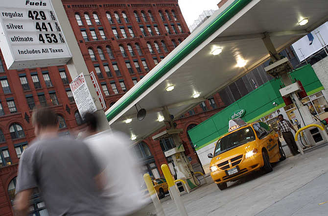 A man pumps petrol into his taxi in New York.