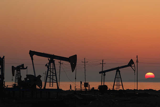Oil derricks are silhouetted against the rising sun on an oilfield in Baku, Azerbaijan.