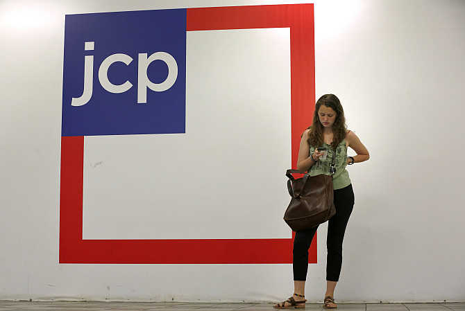 A woman checks her phone outside the entrance of a JC Penney store in New York.