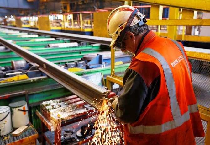 An employee gives finishing touches to a rail at a Tata Steel rails factory.