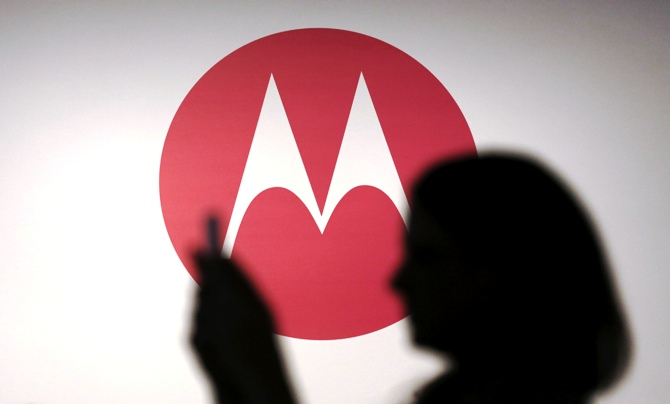 A woman takes a picture in front of a Motorola logo.