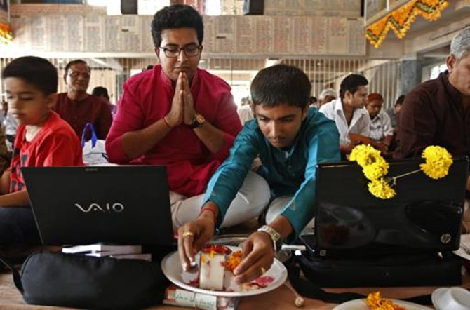 Businessmen offer prayers to Hindu gods in front of their laptops as part of a ritual to worship the Hindu deity of wealth Goddess Lakshmi on Diwali.
