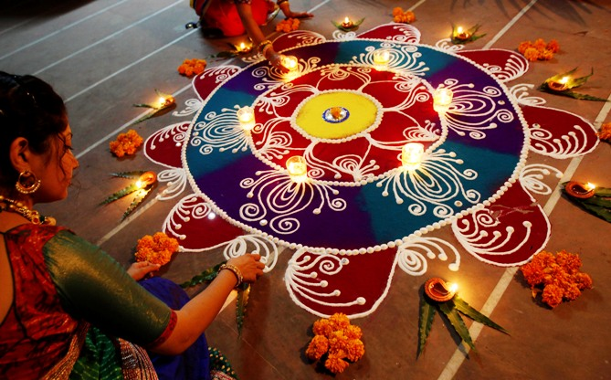 Women arrange oil lamps and flowers around a Rangoli, made from coloured powders, during Diwali in Ahmedabad.