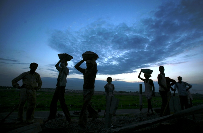 Labourers are silhouetted against the setting sun as they work at a road construction site in Greater Noida on the outskirts of New Delhi.