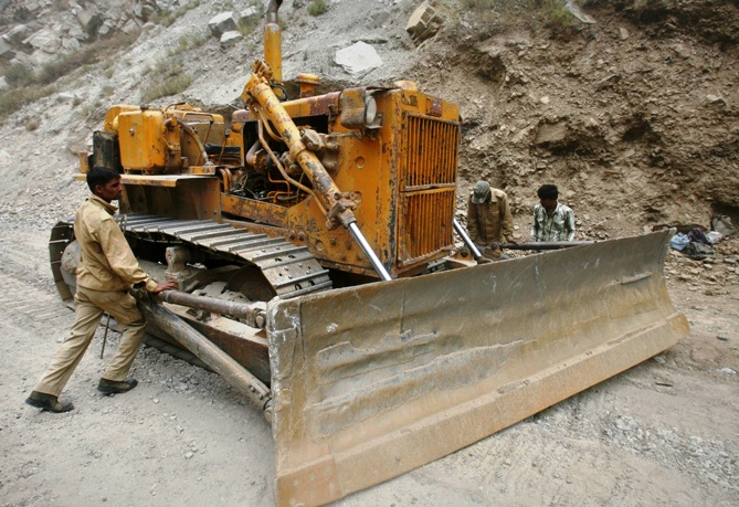 Labourers employed by the Indian army, adjust a bulldozer blade on India's Tezpur-Tawang highway which runs to the Chinese border in China.