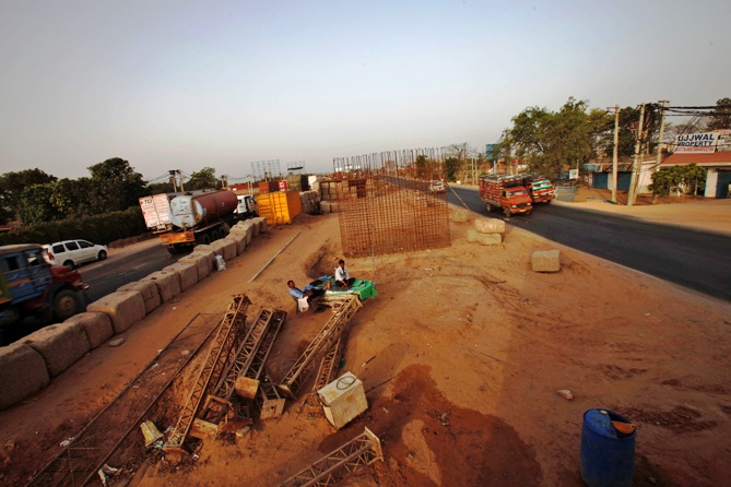 Security guards sit at the construction site of a flyover along a highway at Manesar, about 60 km (38 miles) south of New Delhi.