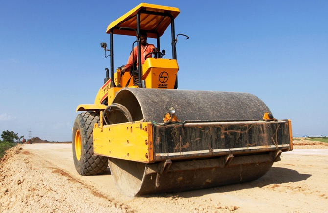 A worker drives a road-roller during road construction near the proposed Ford car plant in Sanand, Gujarat state, September 26, 2011.