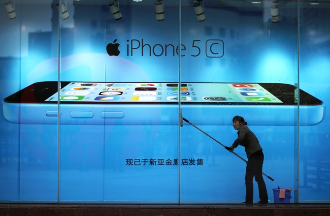 A worker cleans glass in front of an iPhone 5C advertisement at an apple store in Kunming, Yunnan province.