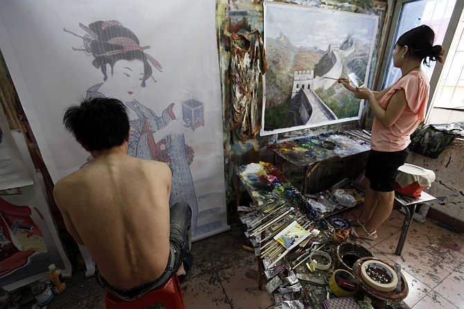 Painters work on oil paintings in a studio at Dafen Oil Painting Village, in Shenzhen, South China's Guangdong province.