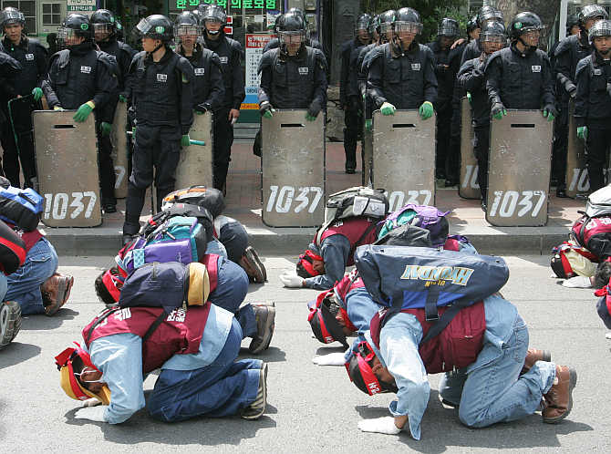 Workers from the Ulsan Construction and Plant Union bow every three steps during a march in Seoul, South Korea. About 600 members of the union and their supporters rallied to demand better working conditions.