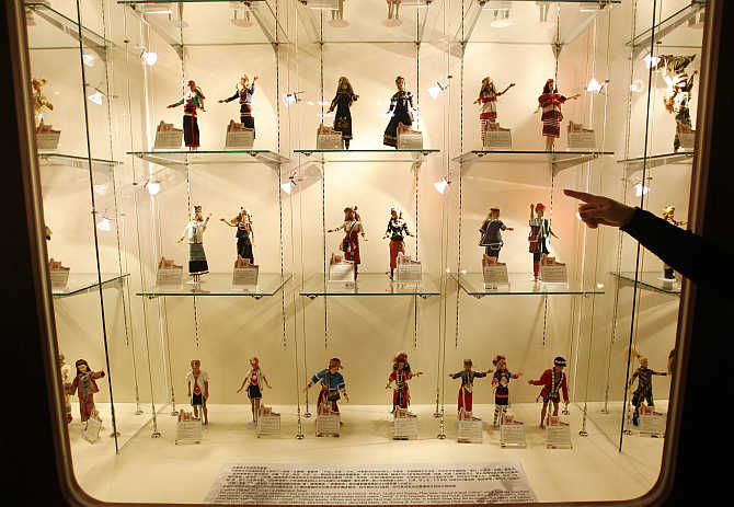 A curator points at dolls inside a display at the Doll Industry Museum in Taishan, Taipei County, Taiwan.