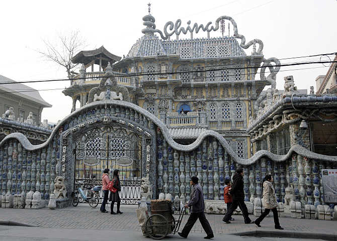 People walk outside the 'China House' in Tianjin, China. The house is decorated with hundreds of millions of ancient porcelain flakes, ancient bowls, dishes and vases, inlaid everywhere in the architecture.
