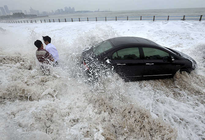 Men wait for help by a stranded car on a flooded seaside road as they are surrounded by waves whipped up by typhoon Bolaven in Qingdao, Shandong province, China.