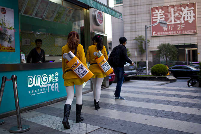 Girls selling lighters walk along a street in downtown Shanghai, China.