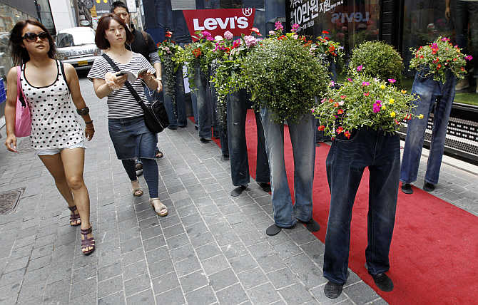 People walk past flowerpots made of old jeans during a recycling campaign at the Myeongdong shopping district in Seoul, South Korea.