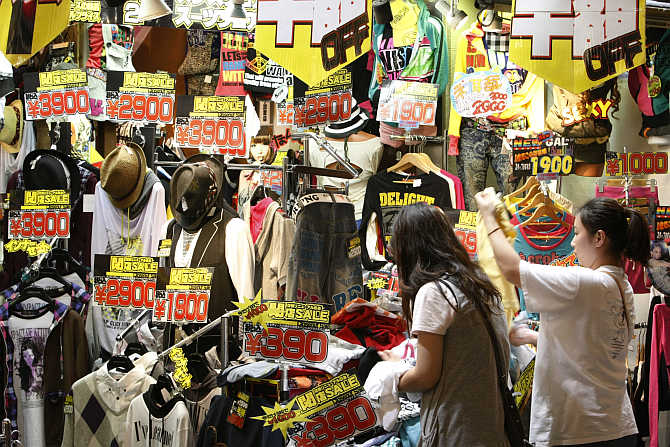 Shoppers browse at a clothing store in the Dotonbori shopping and amusement district in Osaka, Japan.