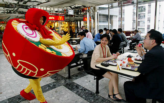 A man dressed as a bowl of noodles greets office workers as he promotes a food fair at a shopping mall in Hong Kong.