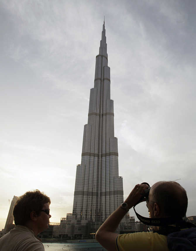A tourist takes photographs of Burj Khalifa, the world's tallest tower, in Dubai, United Arab Emira