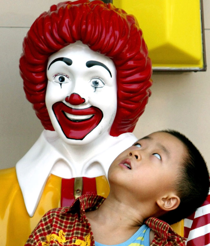 A Chinese boy stares up at a statue of Ronald McDonald in front of a McDonald's Restaurant in Beijing.