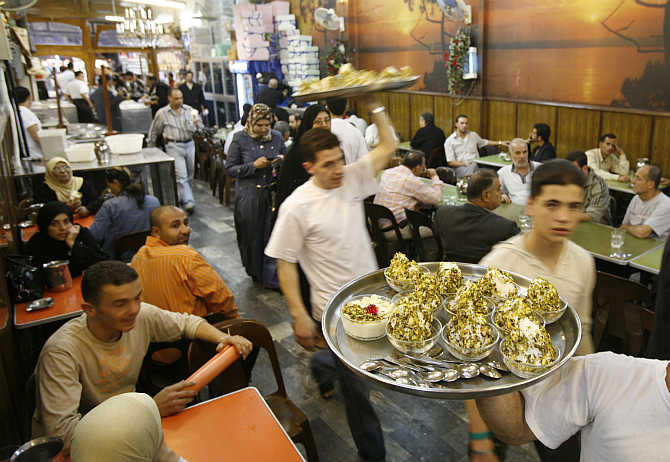 Waiters at Bikdash shop in Old Damascus carry plates of hand made ice-cream, Syria.