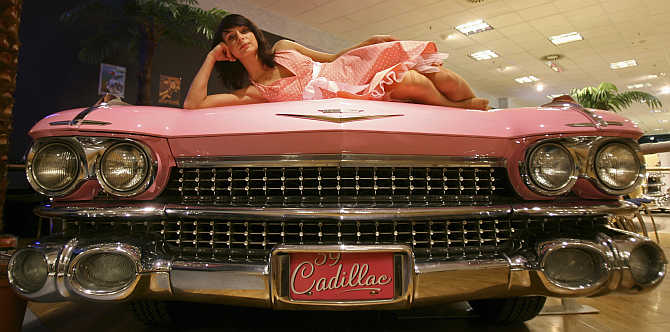 A model poses on the hood of a 1961 Cadillac at the Dream Car exhibition in Budapest, Hungary.