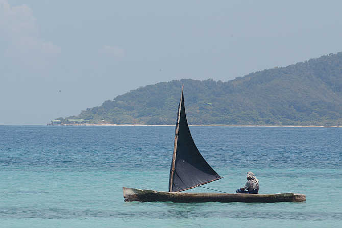 A man steers his canoe offshore of Cayo Cachahuate on the northern coast of Honduras.