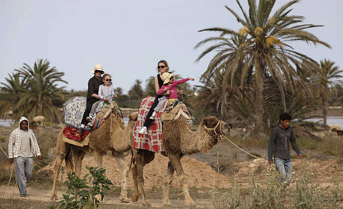 Tourists ride camels on the island of Djerba, Tunisia.