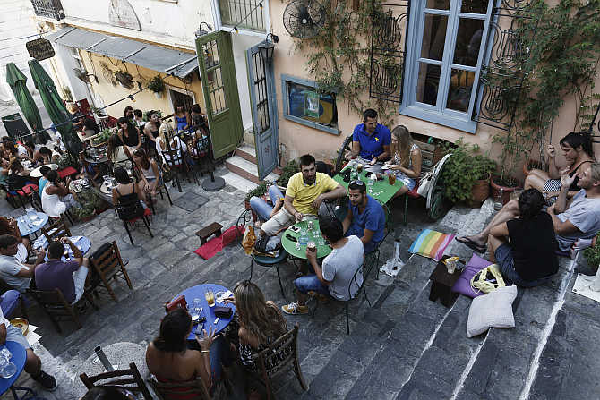 People sit at a cafe at the tourist district of Plaka in central Athens, Greece.