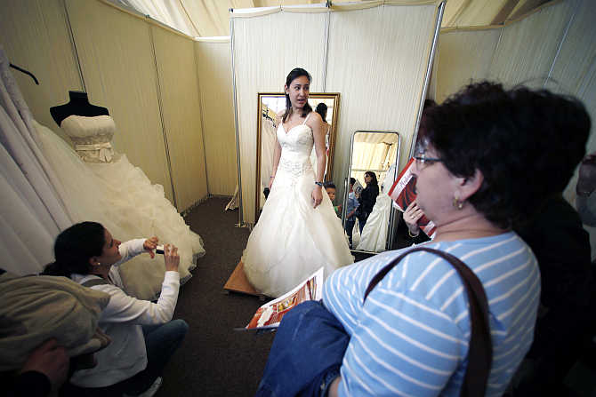 A woman tries on a bridal gown during the E-Marriage Fest wedding fair in Bucharest, Romania.