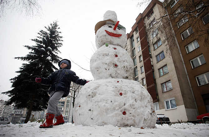 A child plays with a snowman after a snowfall in central Bosnian town of Zenica.
