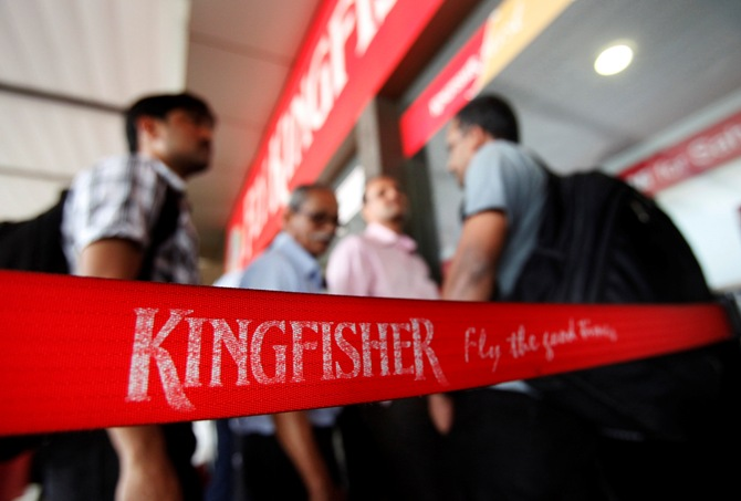 Customers stand at a Kingfisher Airlines reservation office at the domestic airport in Mumbai March 20, 2012.