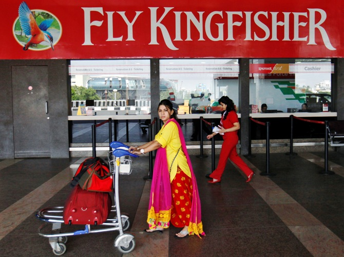 A passenger walks with her luggage in front of a Kingfisher Airlines reservation office at the domestic airport in Mumbai.