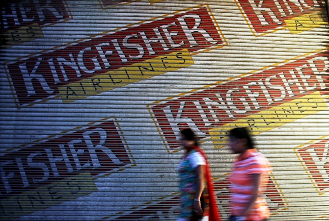 Women walk past a closed booking office of Kingfisher Airlines in New Delhi October 1, 2012.