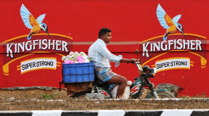A man on a motorbike rides past the factory of United Breweries Ltd (UB) that manufactures Kingfisher beer in Thiruvalluar district of Tamil Nadu.