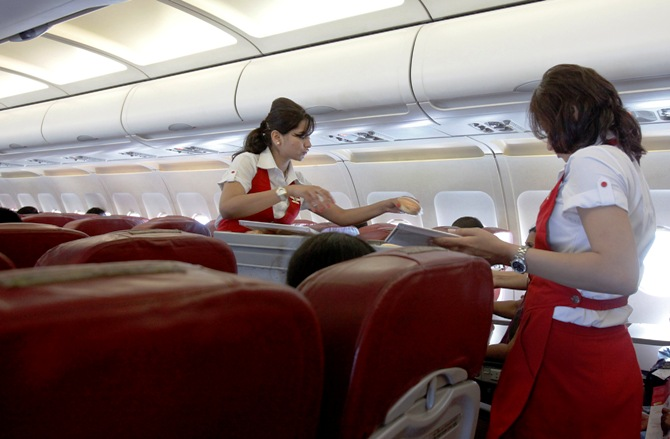 Kingfisher Airlines cabin attendants serve snacks on a flight after takeoff from Mumbai's domestic airport March 20, 2012.