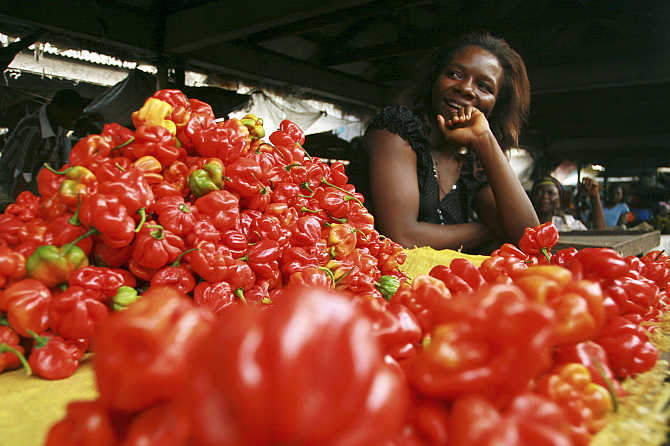 A vendor stands behind her vegetables on sale at a market in Calabar, Delta region, Nigeria.