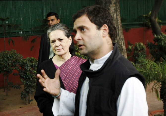 Congress chief Sonia Gandhi (left) watches as her son Rahul Gandhi speaks during a press conference in New Delhi December 8, 2013.