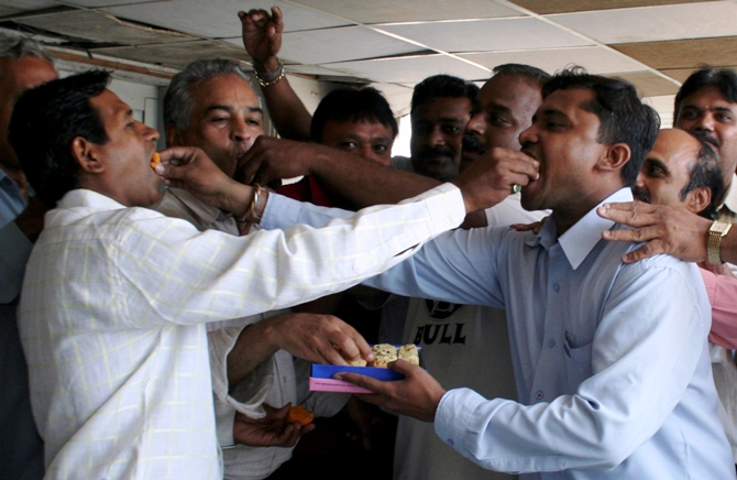 Traders eat sweets inside a brokerage in Ahmedabad.