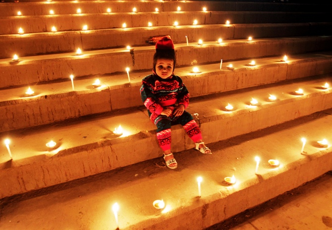 A girl sits on the staircase decorated with lamps and candles on the occasion of Diwali festival in Allahabad.
