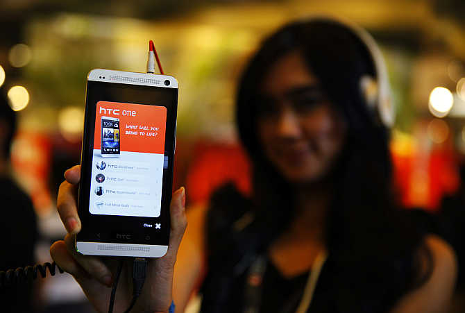 A sales girl displays the HTC One mobile phone at Taman Anggrek Mall in Jakarta, Indonesia.