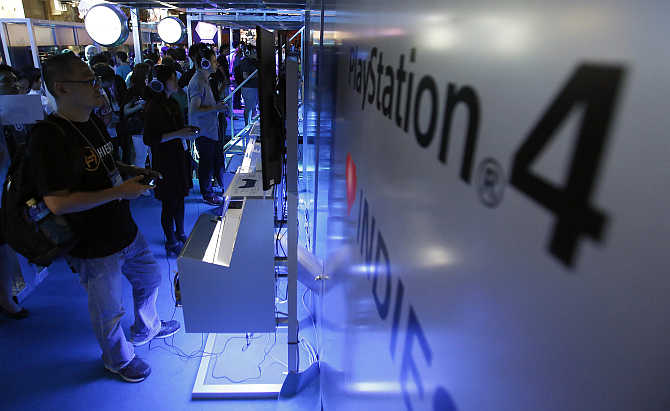 Visitors try out PlayStation 4 game console at the Tokyo Game Show in Chiba, east of Tokyo, Japan.