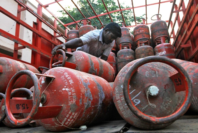 A worker loads empty Liquefied Petroleum Gas cylinders onto a supply truck in Chennai.