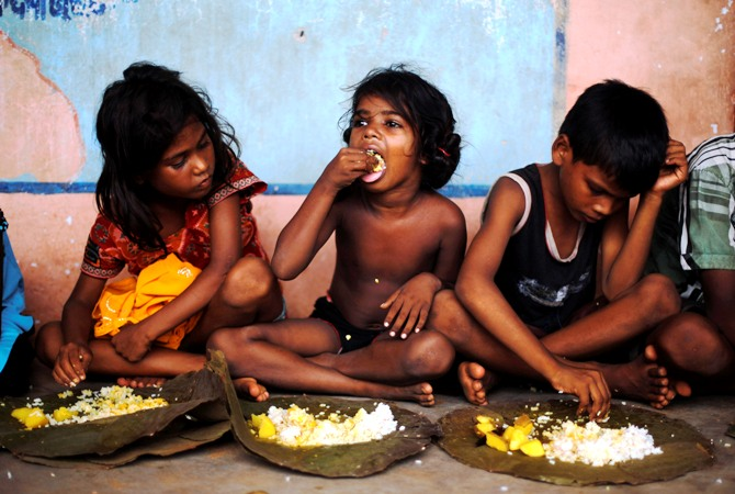 Children eat their lunch in a free meal centre at the cyclone-hit Gopalpur village, in Ganjam district, Odisha.