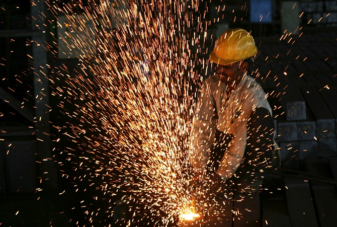 A worker cuts steel bars inside a factory on the outskirts of the southern Indian city of Hyderabad.