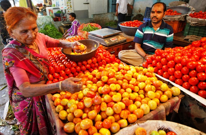 A woman buys tomatoes at a wholesale vegetable market in Ahmedabad.