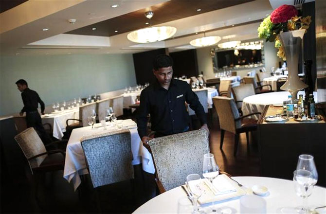 An employee of Le Cirque Signature restaurant prepares a table.