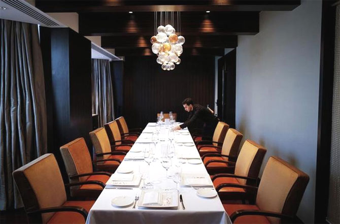 An employee of Le Cirque Signature restaurant prepares a table inside a private dining room in Mumbai.
