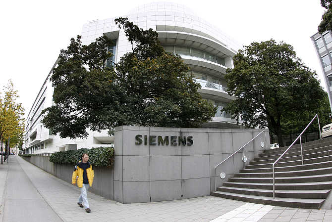 A man passes by Germany's Siemens headquarter in Munich.