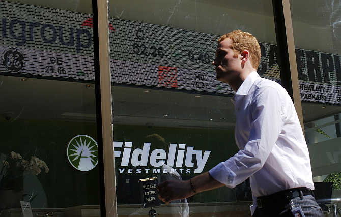 A pedestrian walks past a stock ticker at a Fidelity Investments office in Boston, Massachusetts.